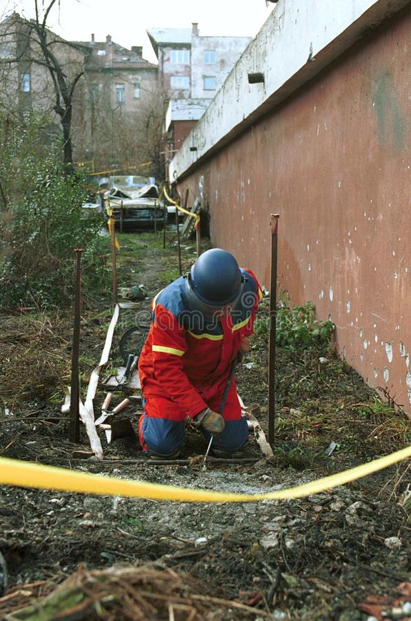 LAND MINE DE-ACTIVATION. SARAJEVO, BOSNIA, 02 OCTOBER 1998 - Norwiegan explosive experts remove land mines from a residential area of the Bosnian capital royalty free stock photography