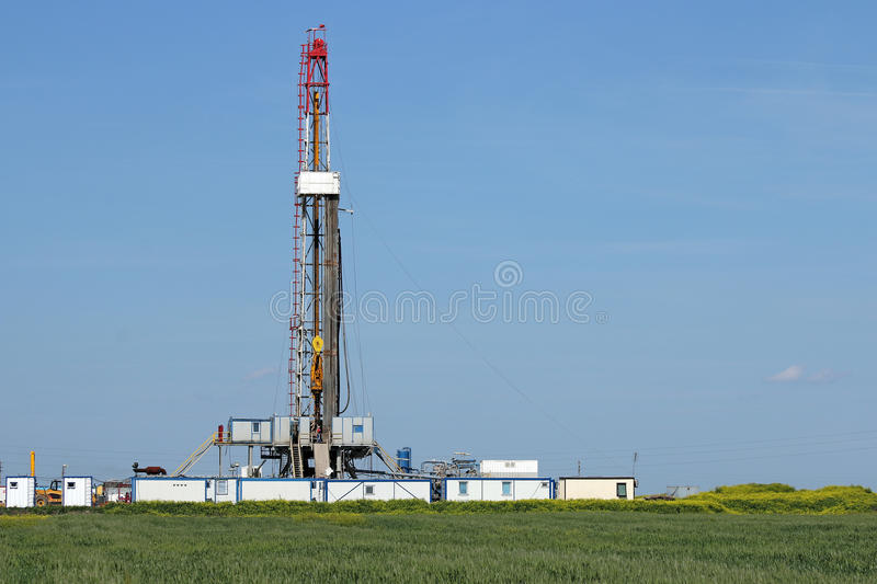 Land oil drilling rig on green field royalty free stock image