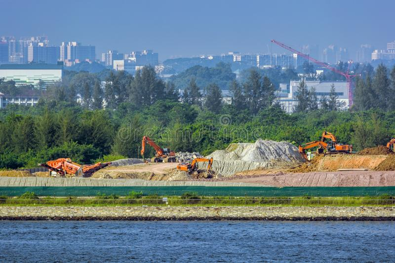 Land reclamation equipment at work. Land reclamation backhoes carry sands and rocks on the shore royalty free stock images