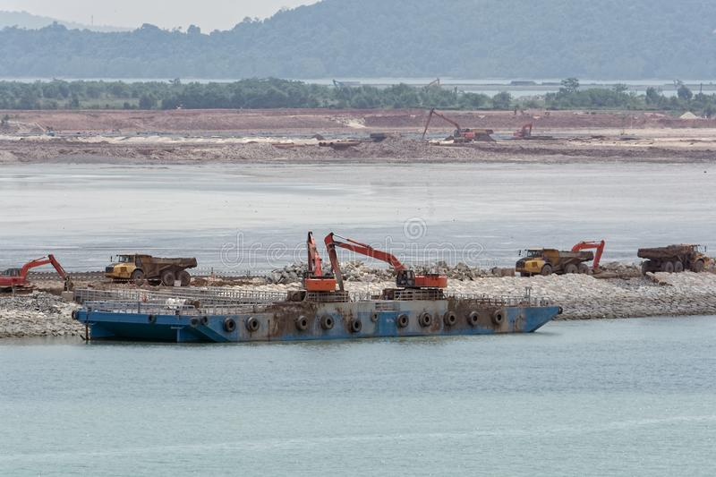 Land reclamation equipment. Workplace of different construction machinery on sea shore to land reclamation from the seas and mangrove swamps stock photos