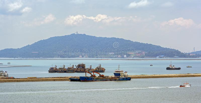 Land reclamation equipment. Workplace of different construction machinery on sea shore to land reclamation from the seas and mangrove swamps stock photography