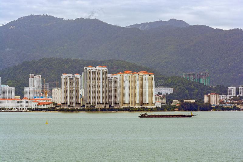 Land reclamation in front of George Town, Penang, Malaysia. Laden Self Discharging Sand Carrier barge anchored in front of land reclamation site in George Town stock images