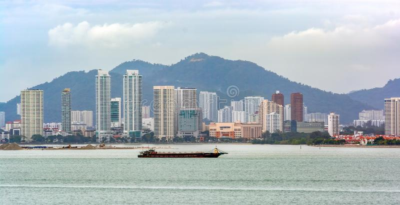 Land reclamation in front of George Town, Penang, Malaysia. Self Discharging Sand Carrier barge anchored in front of land reclamation site in George Town stock images