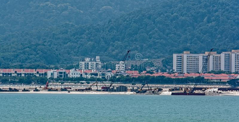 Land reclamation on George Town shore, Penang, Malaysia. Penang coastal land reclaiming activity at Gurney drive, which involves the construction of a new stock photos
