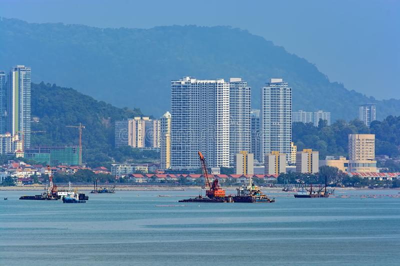 Land reclamation on George Town shore, Penang, Malaysia. Penang coastal land reclaiming activity at Gurney drive, which involves the construction of a new stock photography