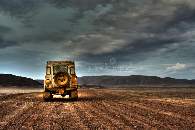 Land Rover Defender on Deserted Road at dusk. A Land Rover Defender photographed on a deserted gravel road in the Messum Crater in North Eastern Namibia stock photography
