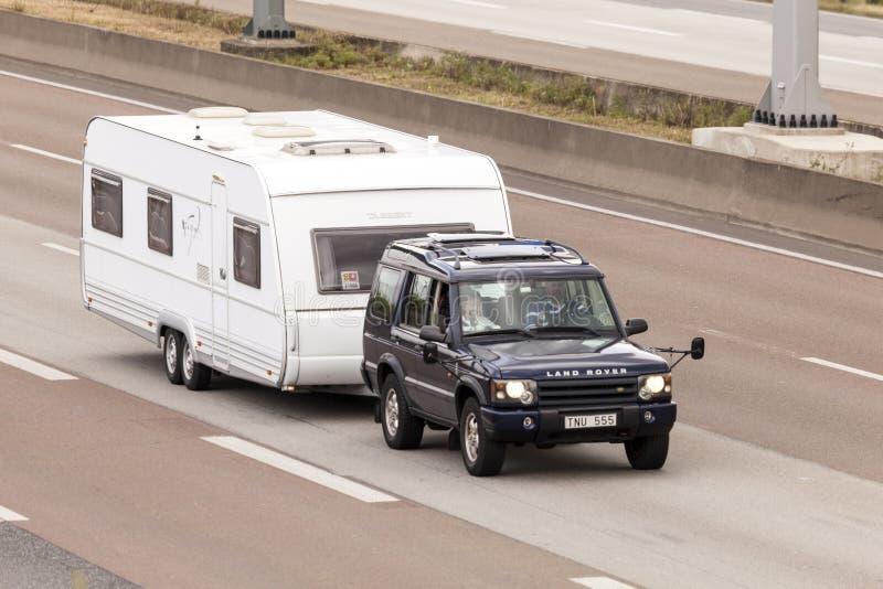 Land Rover Discovery die een caravan slepen stock foto's