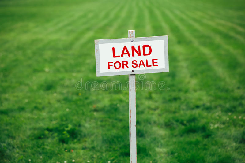 Land for sale sign against trimmed lawn background stock images