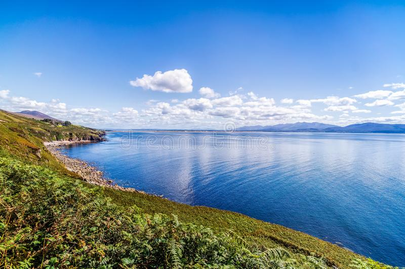Blue sky with white puffy clouds over rocky coastal line and mountains in a distance stock image