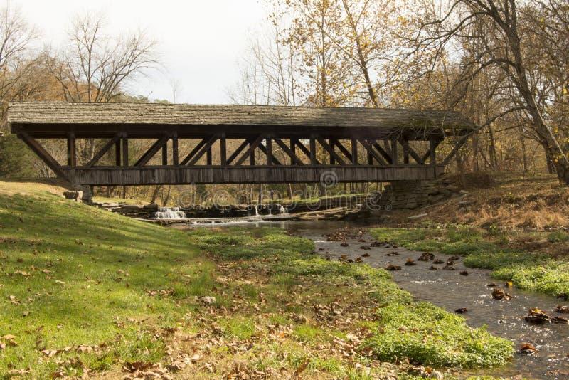 Land täckt bro över den rinnande bäcken royaltyfria foton