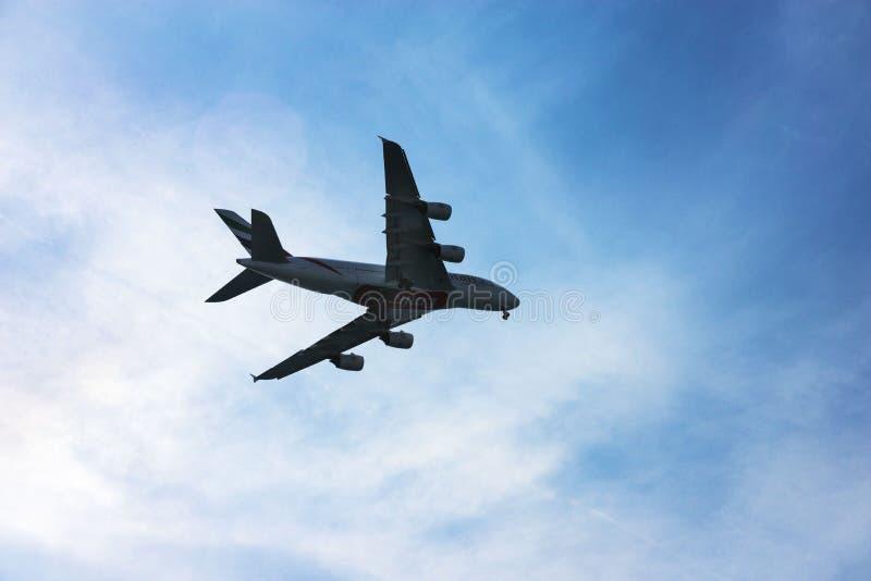 Land van het de passagierslijnvliegtuig van Emirates Airlines het grote grijze Vliegtuig in een blauwe nevel tegen de hemel royalty-vrije stock fotografie