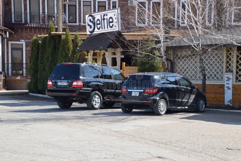 Landa kryssaren Prado från Toyota och Mercedes b200 Bilen parkeras nära kafét fotografering för bildbyråer
