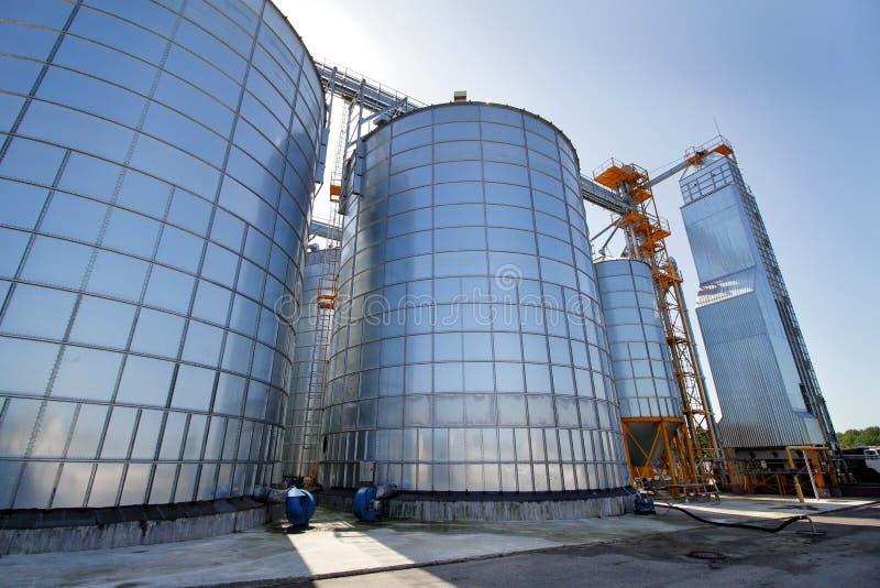 Landbouw silo's De Buitenkant van de bouw Opslag en het drogen van korrels, tarwe, graan, soja, zonnebloem tegen de blauwe hemel stock foto's