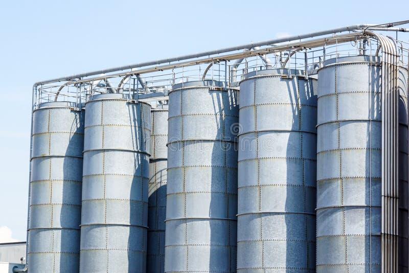 Landbouw silo's De Buitenkant van de bouw Opslag en het drogen van korrels, tarwe, graan, soja, zonnebloem tegen de blauwe hemel stock afbeeldingen