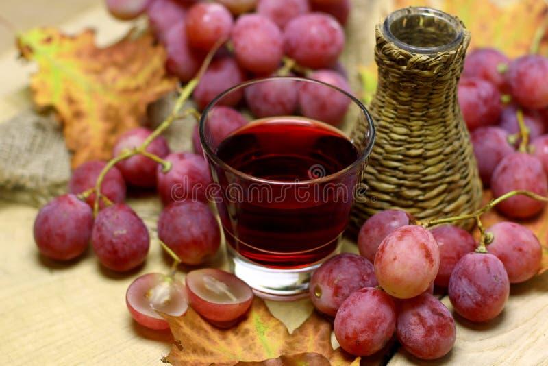 Landbouwbedrijf gemaakte wijnen rieten fles en druiven stock fotografie