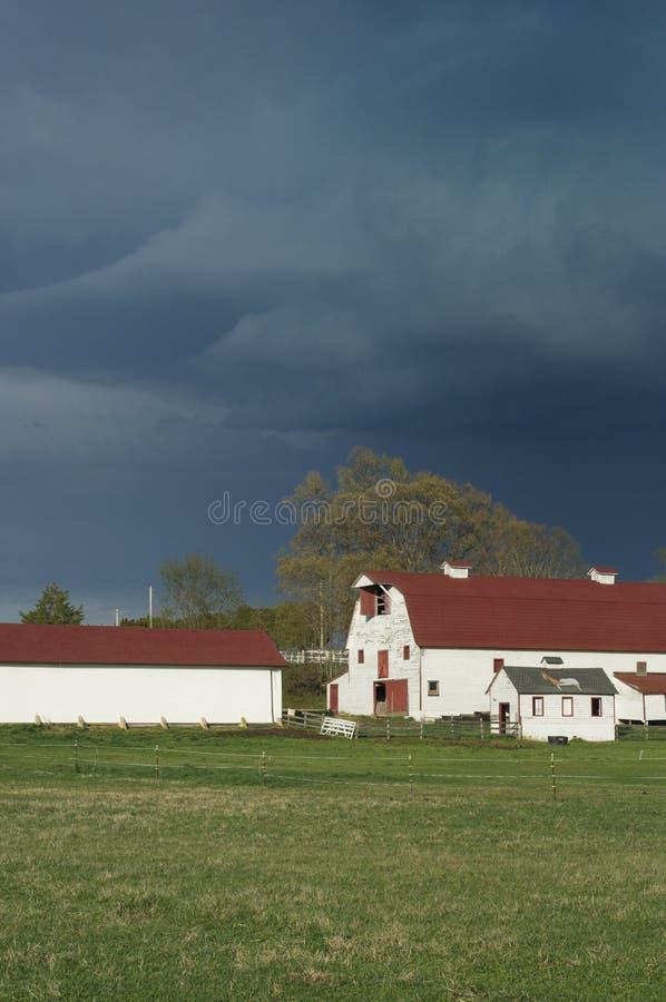 Landbouwbedrijf met inkomend onweer stock fotografie