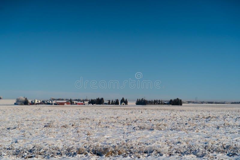 Landbouwbedrijfhuis en silo met sneeuw behandelde gebieden stock afbeelding