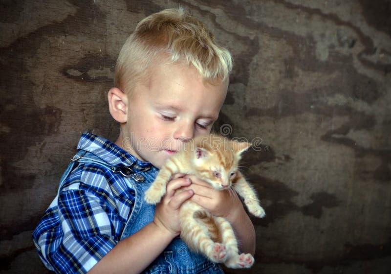 Landbouwbedrijfjongen die een katje houden en de liefde genieten van royalty-vrije stock fotografie