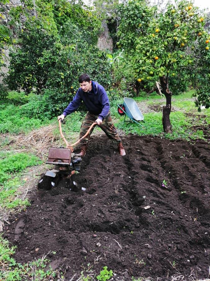 Landbouwer aan het werk die maagdelijke grond ploegen stock afbeelding
