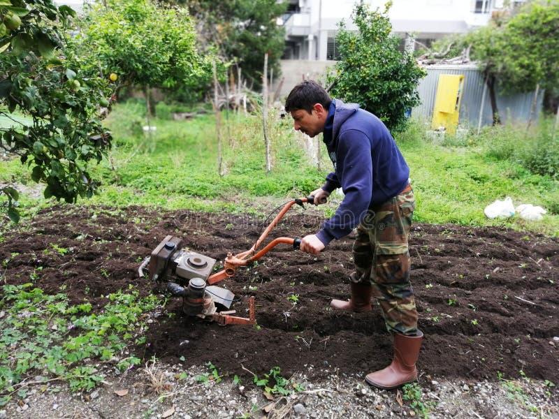 Landbouwer aan het werk die maagdelijke grond ploegen stock afbeeldingen