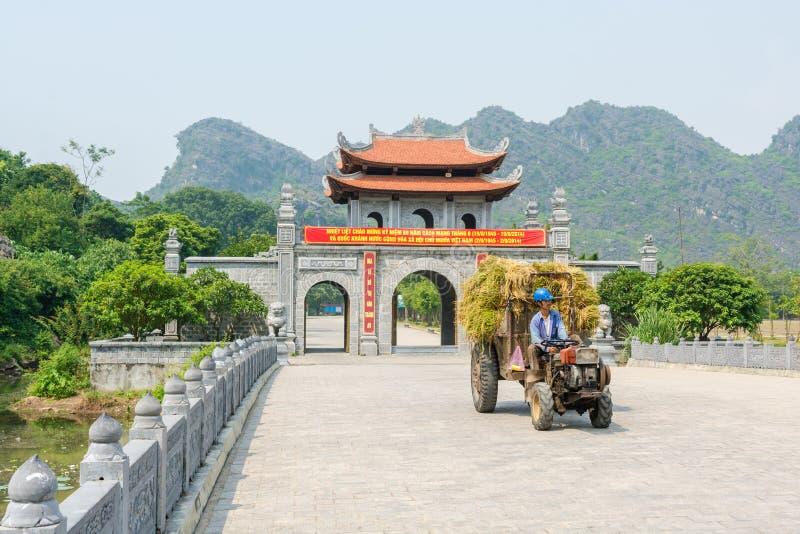 Landbouwer bij het oude roestige tractor drijven voor oude poortnea stock afbeeldingen