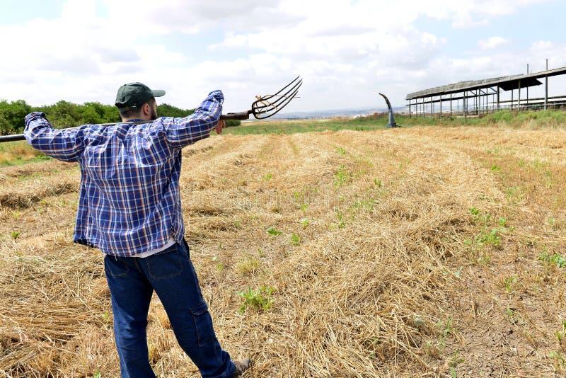 Landbouwer die een vork houden en op zijn gebied kijken stock afbeeldingen