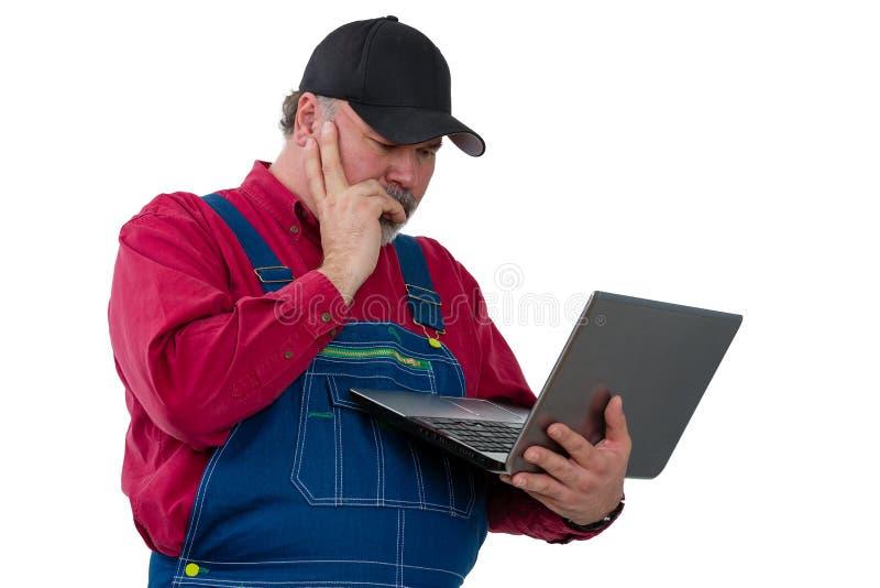 Landbouwer die lezend een handbediende laptop computer bevinden zich stock fotografie