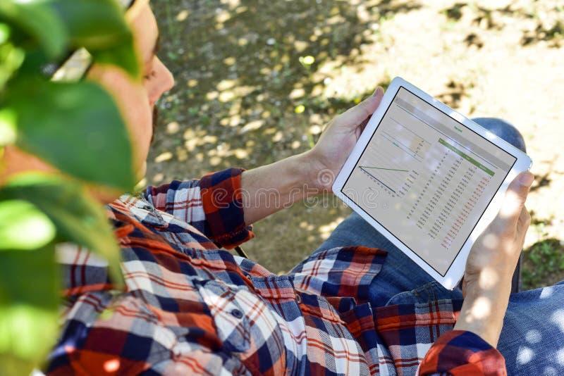 Landbouwer die sommige grafieken in een tablet waarnemen stock afbeeldingen