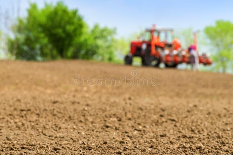 Landbouwer die tractor met zaaimachine op gebied herstellen royalty-vrije stock foto