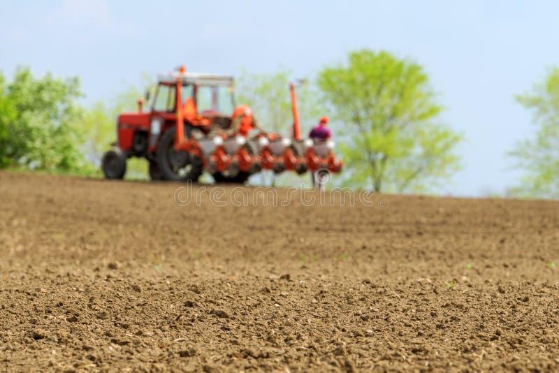 Landbouwer die tractor met zaaimachine op gebied herstellen royalty-vrije stock afbeeldingen