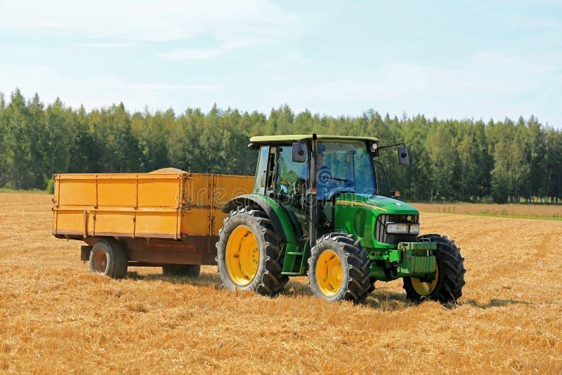 Landbouwer Driving John Deere 5820 Tractor en Aanhangwagen stock foto