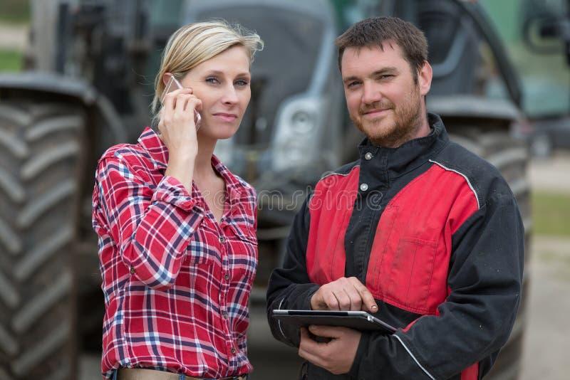 Landbouwer en technicus die samen met elektronika werken stock foto's