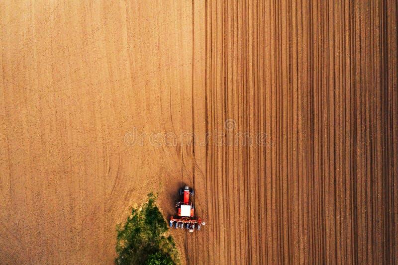 Landbouwer en tractor met zaaimachine van hommel POV royalty-vrije stock afbeeldingen