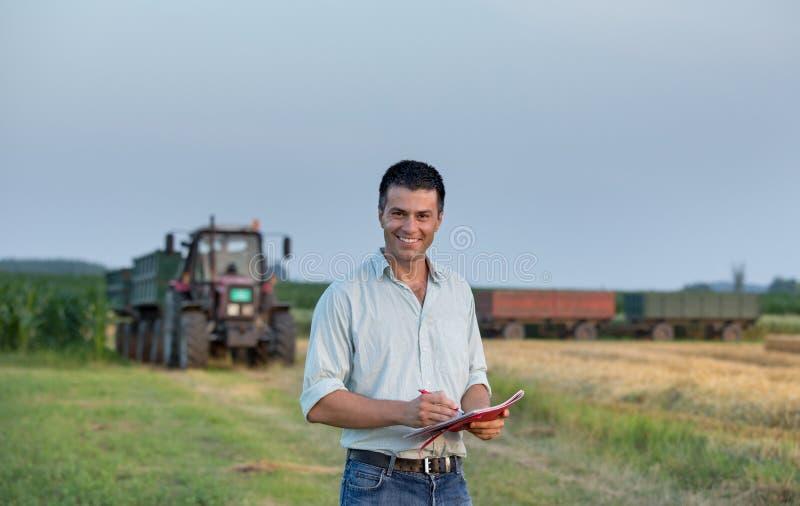 Landbouwer en tractor op gebied royalty-vrije stock afbeeldingen