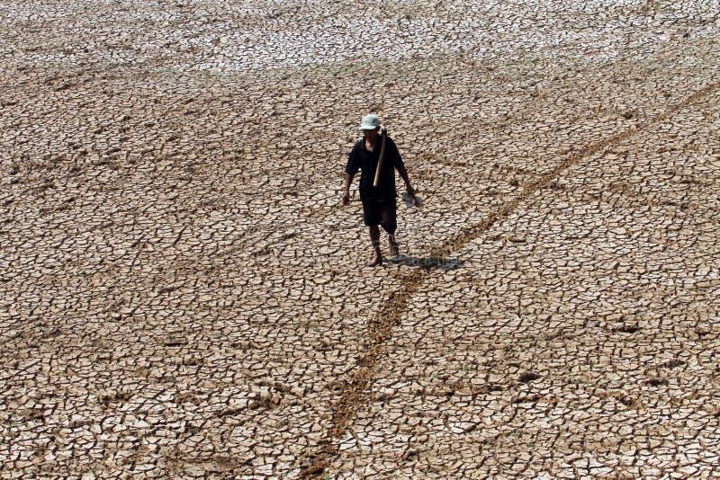 Landbouwer het lopen onder de grond droogt wegens verlengd uit droug royalty-vrije stock foto