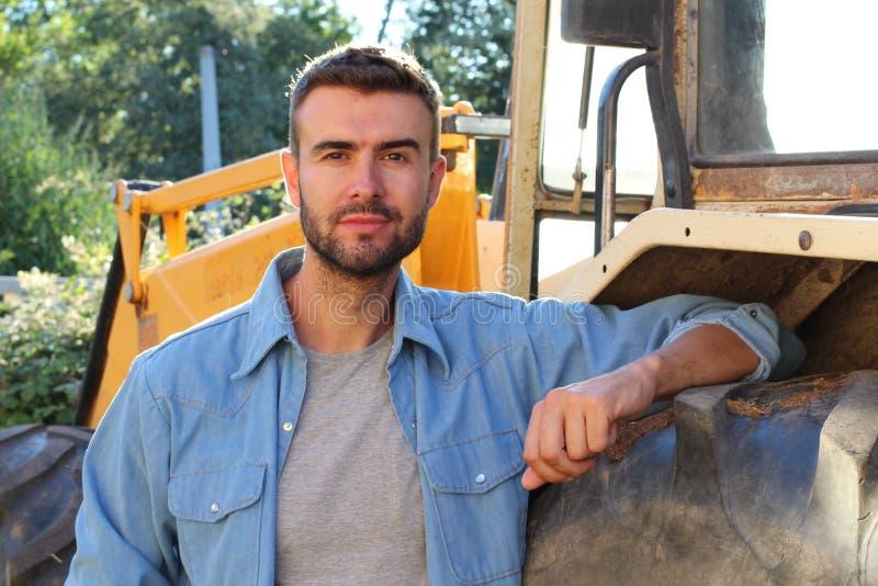 Landbouwer het stellen voor zijn tractor stock afbeeldingen