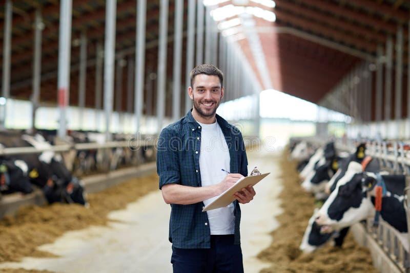 Landbouwer met klembord en koeien in koeiestal op landbouwbedrijf royalty-vrije stock foto's