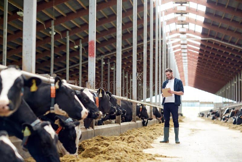 Landbouwer met klembord en koeien in koeiestal op landbouwbedrijf stock afbeelding