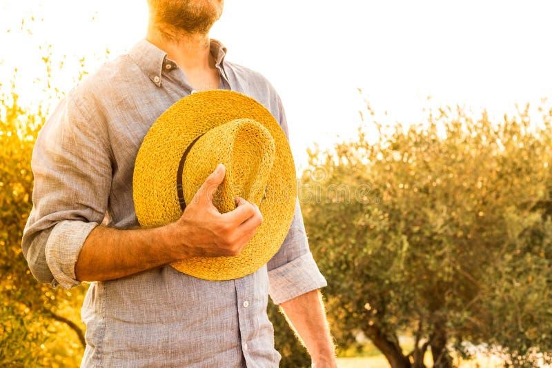 Landbouwer met strohoed voor een olijfgaard - landbouw royalty-vrije stock afbeelding