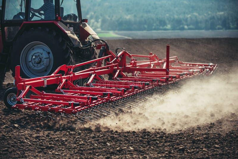 Landbouwer met tractor het zaaien gewassen bij gebied stock fotografie