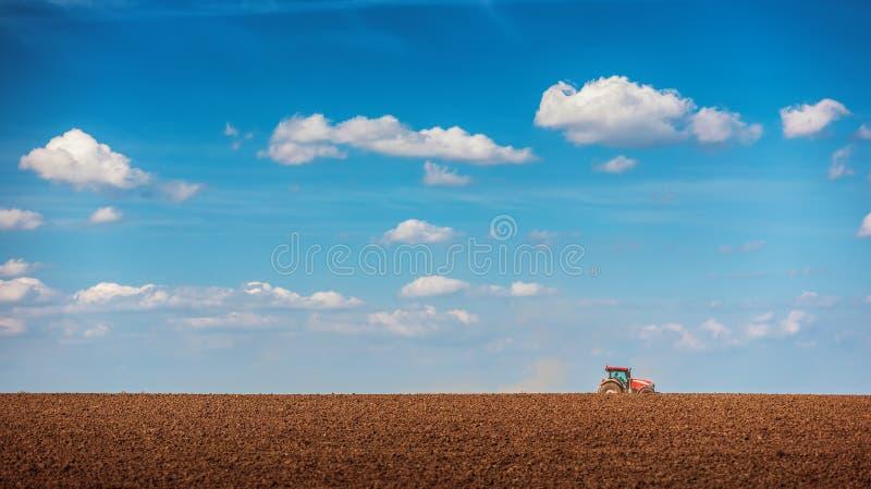 Landbouwer met tractor het zaaien gewassen bij gebied royalty-vrije stock foto