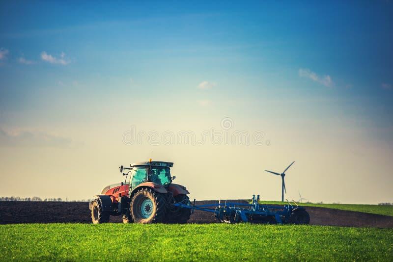 Landbouwer met tractor het zaaien gewassen bij gebied stock foto