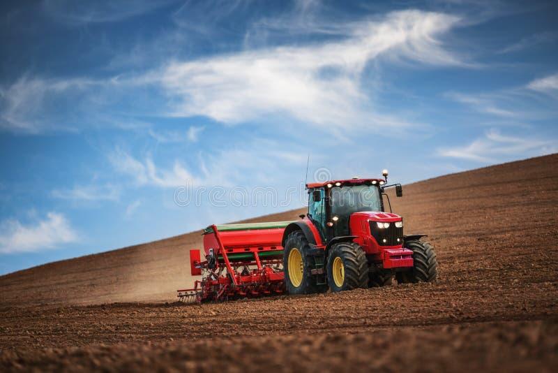 Landbouwer met tractor het zaaien gewassen bij gebied royalty-vrije stock foto's