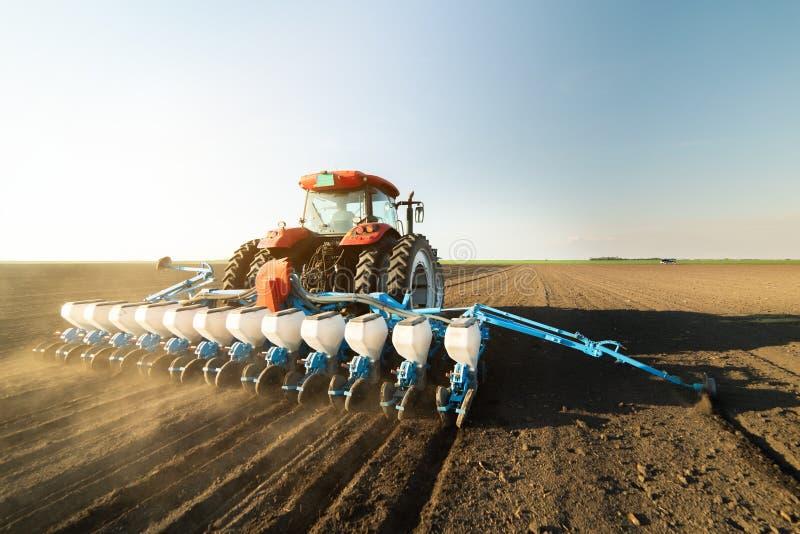 Landbouwer met tractor het zaaien sojagewassen bij landbouwgebied stock afbeeldingen
