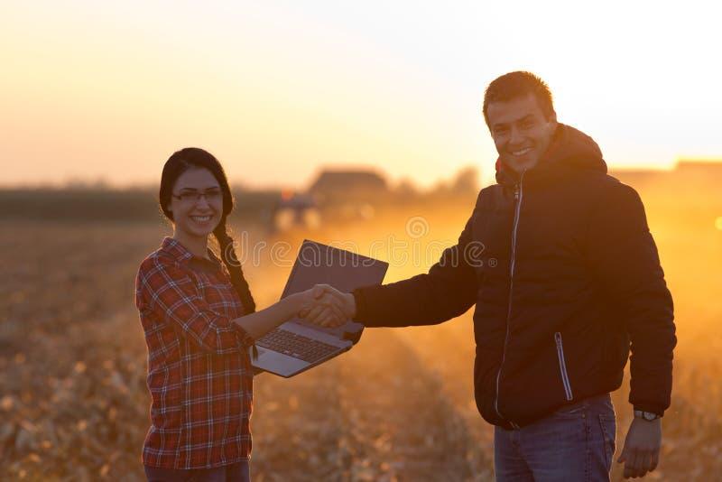 Landbouwers die hnds bij zonsondergang schudden royalty-vrije stock afbeeldingen