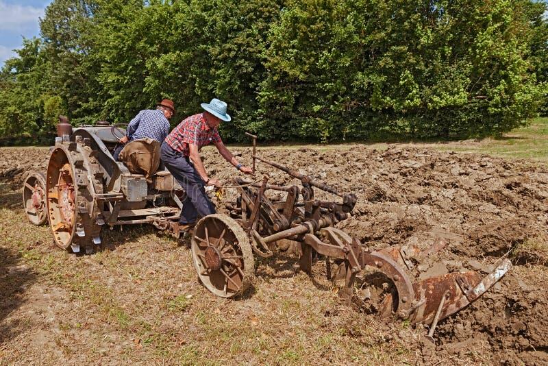 Landbouwers die met een oude tractor ploegen royalty-vrije stock fotografie