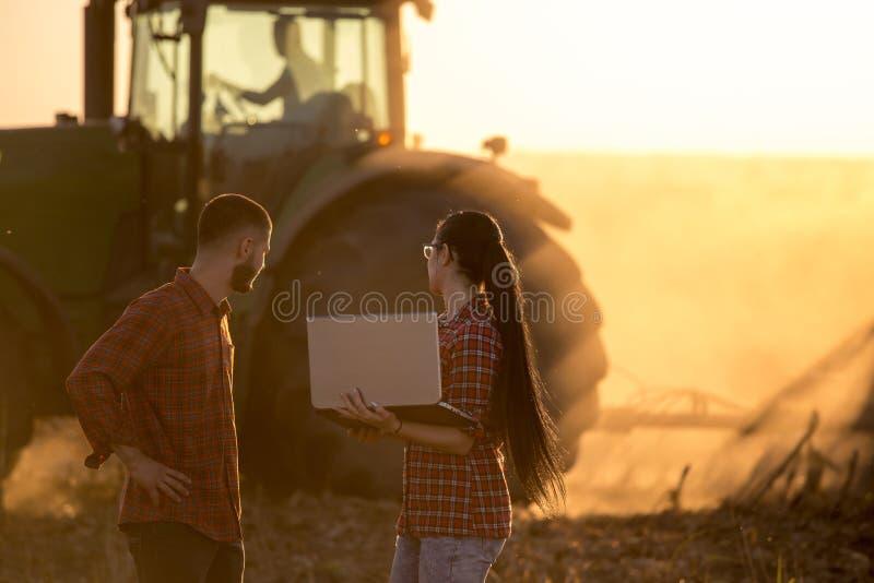 Landbouwers met laptop op gebied bij zonsondergang royalty-vrije stock afbeeldingen