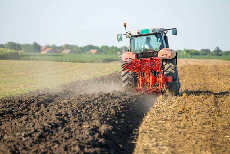 Landbouwers ploegend stoppelveld met rode tractor stock foto