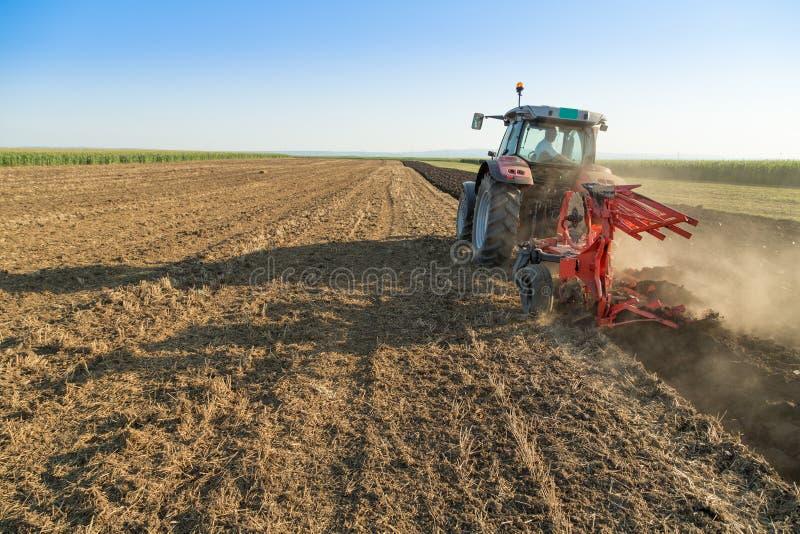 Landbouwers ploegend stoppelveld met rode tractor royalty-vrije stock fotografie
