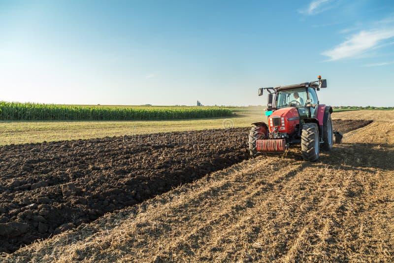 Landbouwers ploegend stoppelveld met rode tractor stock afbeeldingen
